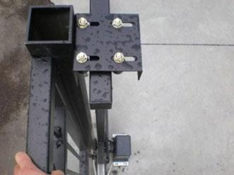 Установленная на откатные ворота регулируемая направляющая роликовая скоба